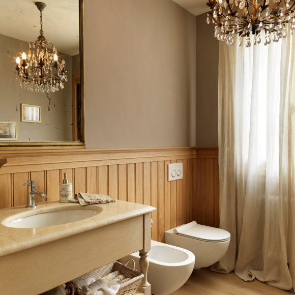 Bagno in appartamento a Brescia con boiserie in rovere tinto. Piano in marmo.