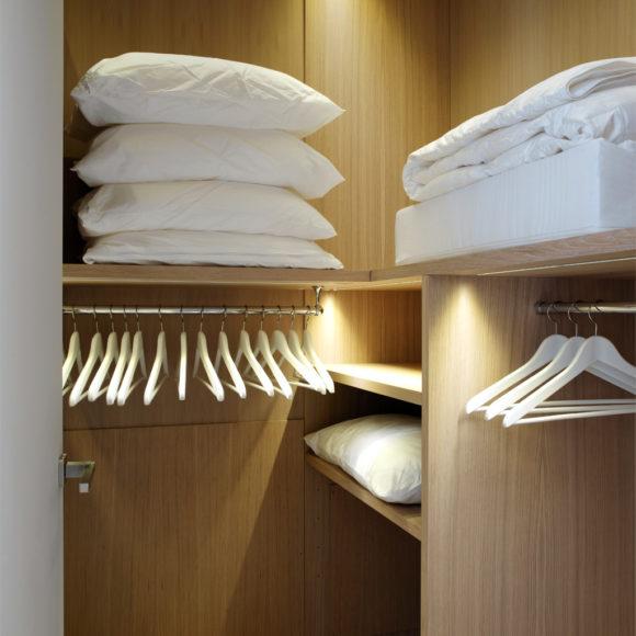 Cabina armadio in appartamento sul Lago di Garda. Su misura, rovere sbiancato e illuminazione.