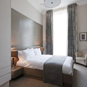 Camera in hotel a Londra con parete in rovere spazzolato e armadio laccato bianco.