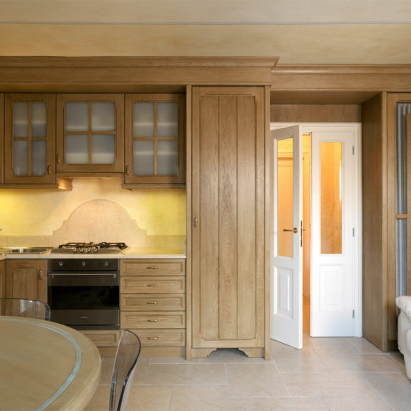 Cucina artigianale classica in legno di rovere tinto, con porta laccata bianca opaca. Lago di Garda.