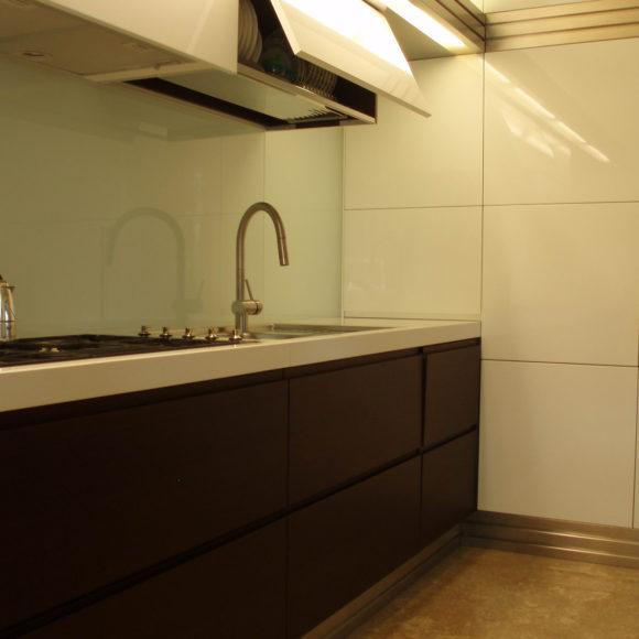 Cucina moderna laccata bianca lucida e marrone. In abitazione a Brescia centro.